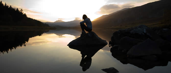 A girl sits on a rock on a lake shore as the sun sets in the distance