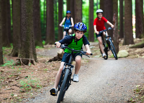 Two young kids ride their mountain bikes down a track