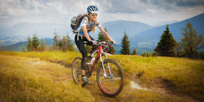 A woman rides down a wilderness track with hills in the background